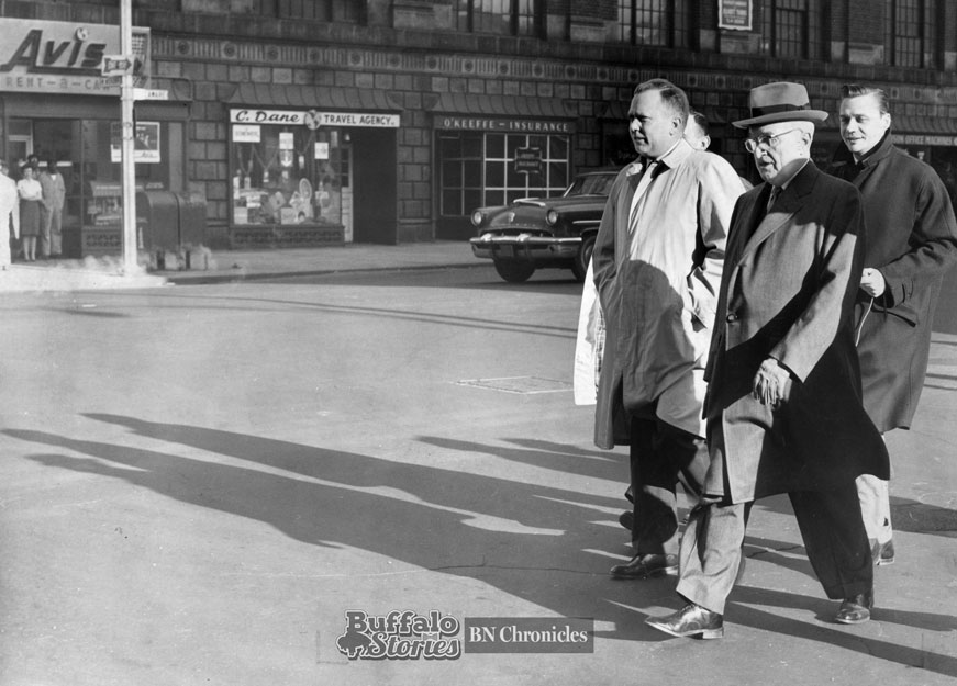Former President Harry S Truman takes one of his famous strolls along Delaware Avenue, accompanied by Buffalo Police Detective Sgt. Joseph McCarthy. In the background is the Statler Garage, a parking ramp fronted with street level retail, kitty-corner from the Hotel Statler at the corner of West Mohawk and Delaware. It was torn down in 1992.