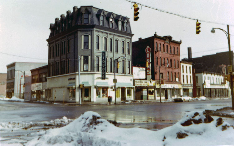 At the top of the page is Charles Birchfields Rainy Night (1929-30). This photo was one of many taken by artist James Vullo in the mid-70s depicting the real life places depicted in Burchfields paintings and sketches. (Charles E. Burchfield Archives) Below, the intersection of Ellicott and Broadway as it looks today.